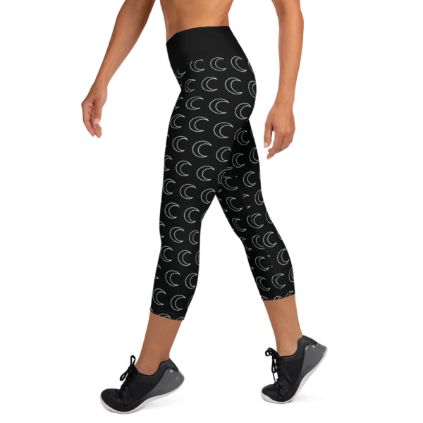 woman wearing black yoga capri leggings with white crescent moon pattern